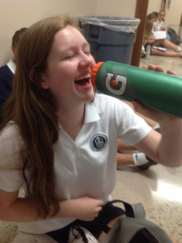 Morgan playfully pretends to drink from her gatorade bottle.