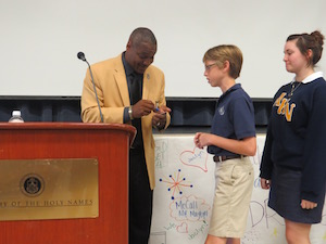Derrick Brooks autographed and gave out football cards to the students who volunteered to answer his questions.