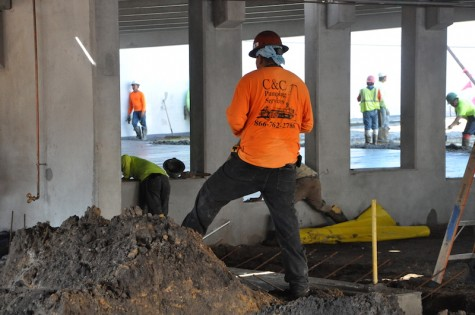 Construction workers filling in the bottom level pavement of the parking garage. PhotoCredit: Riley Gillis