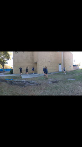 LAX girls warming up before their big tryout. The players practice throwing the ball on the wall and catching it with their sticks.