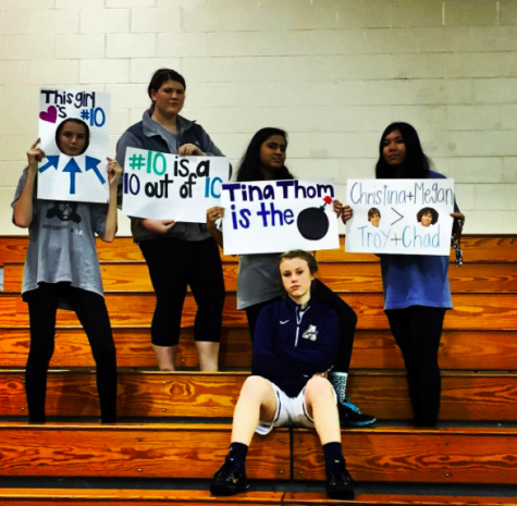 Fans cheer on their friend with posters at an Academy basketball game.