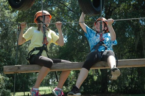 Juniors Caitlyn Helms (left) and Meghan Curing (right) test their teamwork skills on Dayspring's newest rope challenge. With tires and small ladders, this difficult activity requires teams of two to climb up the swinging tires and scale the ladders to reach the top of the structure. Photo Credit: Haley Palumbo (used with permission)