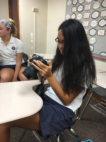 Laura prepares her camera to capture many memories at Senior Reflection day.