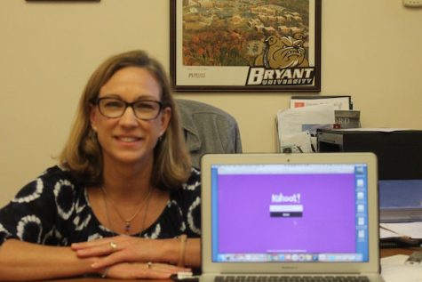 Photo Credit: Julia Prince (Achona Online) Collins similes next to her computer showing off her favorite website. She loves using kahoot to engage students.