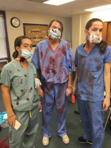 Seniors Anna Padron, Abby Morris, and Ally Wehle played convincingly evil doctors, thanks to Traud and her makeup team. Photo Credit: Alex Smith/Achona Online